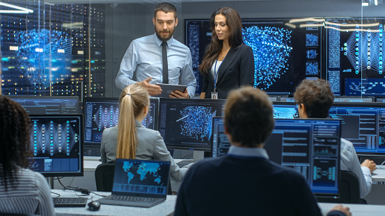 Head Of The Department And Project Manager Discuss Work Process Using Data On A Tablet Computermultiethnic Team Of Engineers Working At Their Workstationdisplays Show Working Model Of Neural Network Stock Photo - Download Image Now