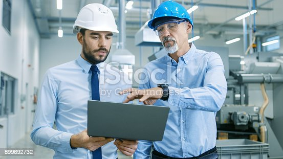 istock Head of the Project Holds Laptop and  Discusses Product Details with Chief Engineer while They Walk Through Modern Factory. 899692732