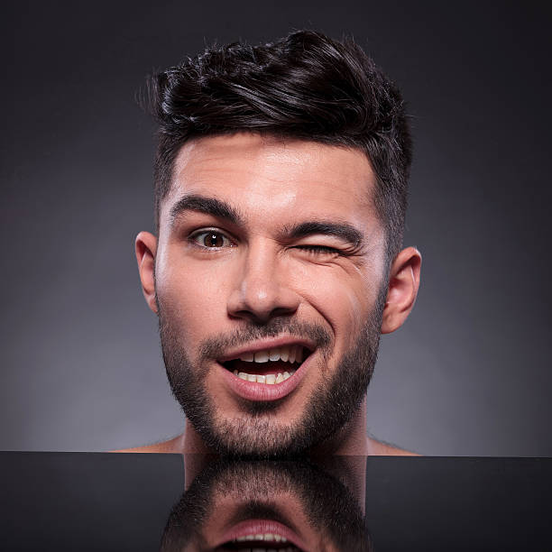 head of winking young man stock photo