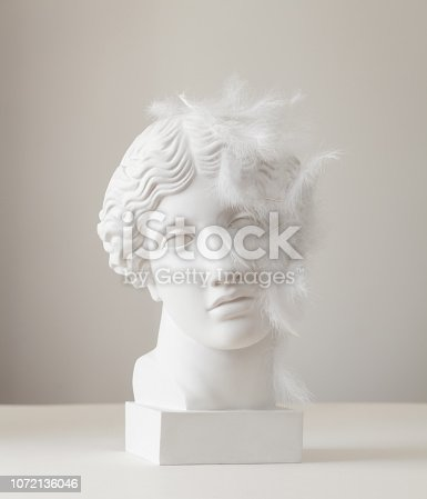 Antique head sculpture with attached feathers