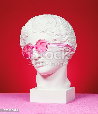 Antique head sculpture wearing pink eyeglasses