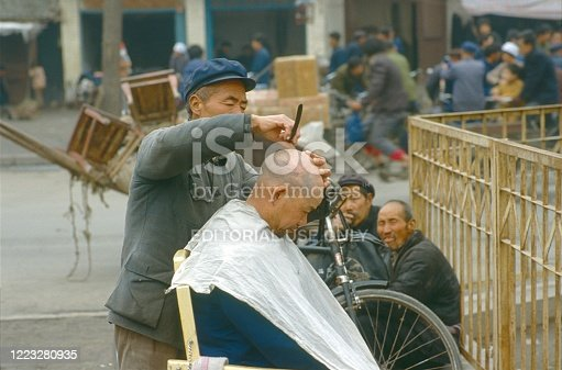 China (exact location unfortunately not known), 1985. Street scene with outdoor head shaving in a Chinese city. Also: hairdresser and customers.