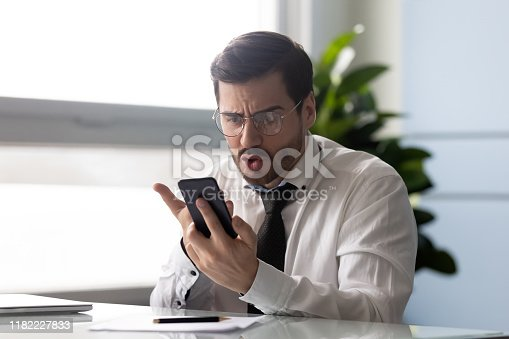 502723248 istock photo Head shot angry manager annoyed by phone problem. 1182227833