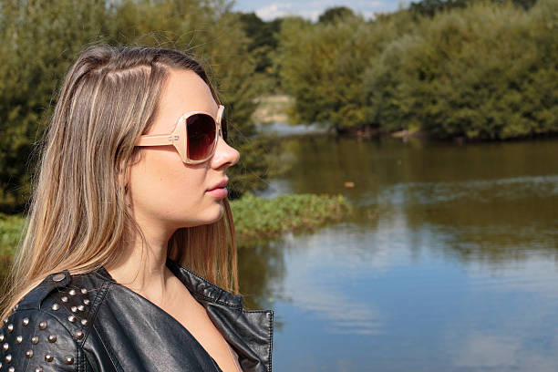 blonde woman sunglasses against water outdoor polish girl - whiteway polish outdoor girl stock photos and pictures