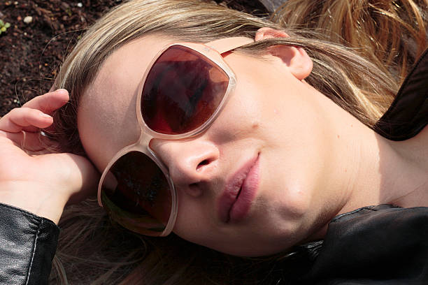 sunglasses eyes closed blonde woman lying down outdoor polish girl - whiteway polish outdoor girl stock photos and pictures