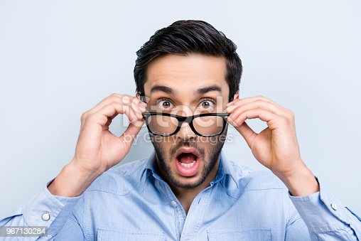 istock OMG! WTF! Head shot of shocke  funny guy with black hair wide open mouth big-eyed looking out glasses on face isolated on grey background 967130284