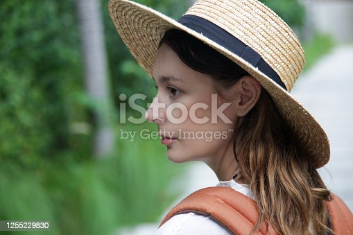 Head shot of tourist woman wearing straw hat and orange backpack on her summer vacation. Close up outdoor portrait of caucasian woman.
