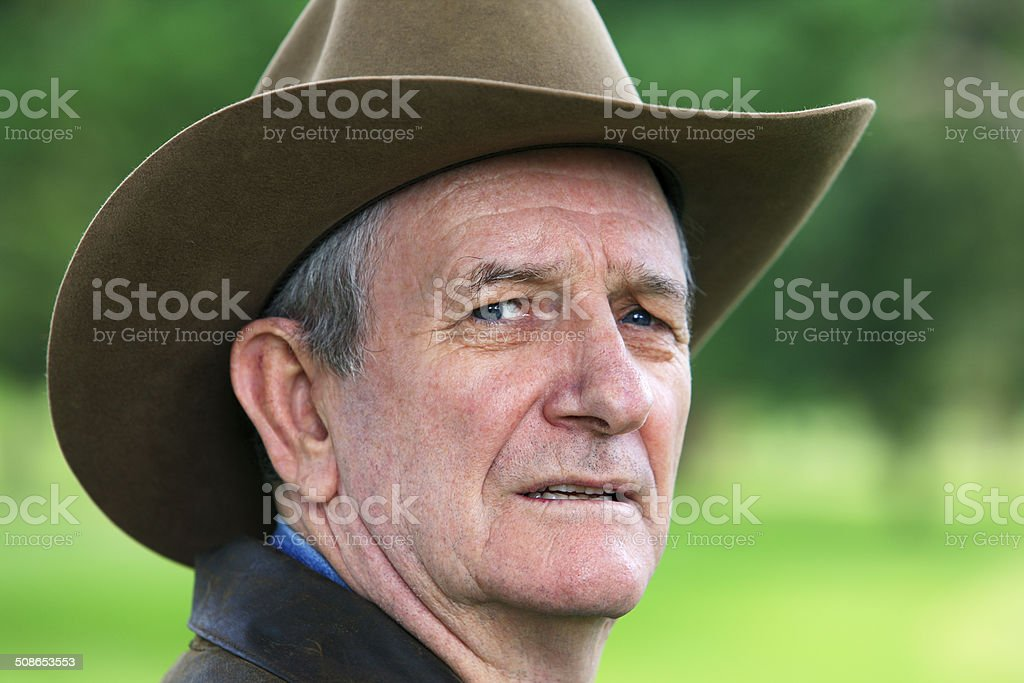 Head shot of worried rancher looking over right shoulder stock photo