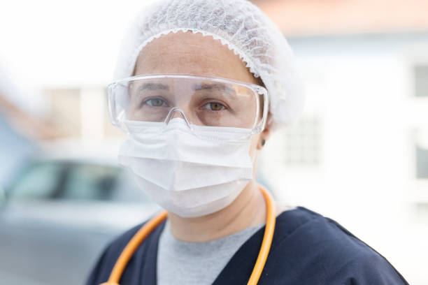 Head shot of young woman with protective mask, glasses and stethoscope in a medical outfit