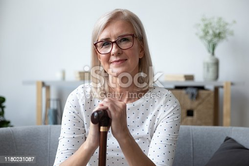 Head shot portrait beautiful older woman in glasses with wooden cane sitting on couch at home, mature female holding hands on walking stick, looking at camera, older people healthcare concept