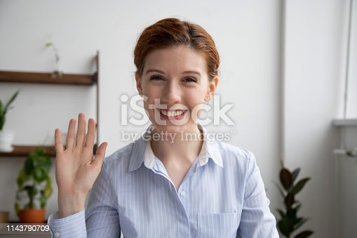 Head shot portrait of attractive smiling businesswoman waving hand, looking at camera, making video call with webcam, greeting, business coach recording video for vlog, saying hello