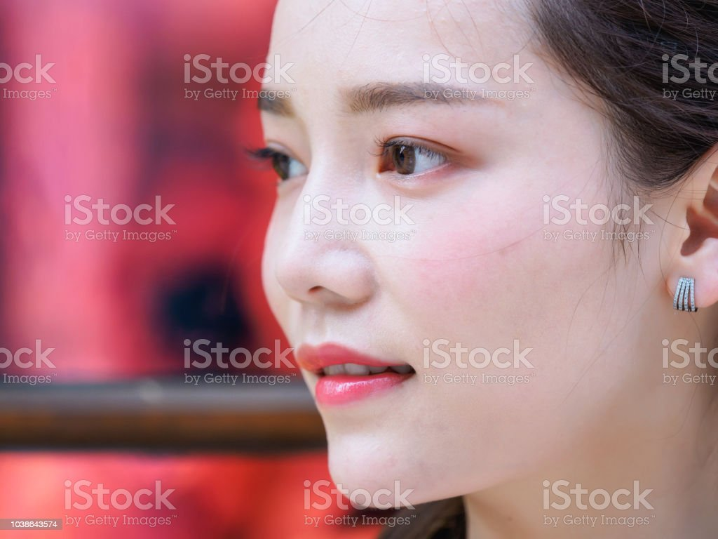 Head shot portrait of beautiful Chinese young woman looking aside, side view, focused on the eyes. - foto stock