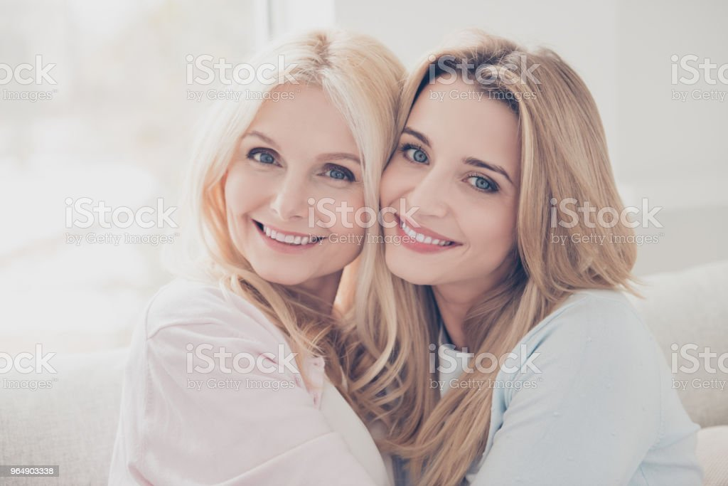 Head shot portrait of cute lovely cheerful pretty mother and daughter enjoying time together looking at camera celebrating mother day spending free time indoor royalty-free stock photo
