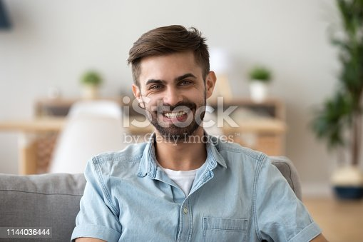 Head shot portrait of happy smiling millennial man sitting on comfortable sofa in living room, looking at camera, successful confident freelancer, excited guy posing for photo at home