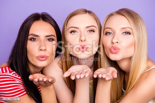 Head shot portrait of lovely sweet girls blowing kisses with pout lips palm at camera isolated on vivid violet background