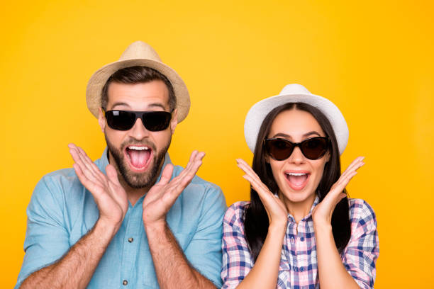head shot portrait of surprised glad traveler in straw hats black eyeglasses with wide open mouth holding palms near face isolated on vivid yellow background - smile woman open mouth foto e immagini stock