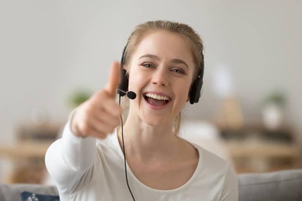 頭のショットヘッドセットで肖像笑顔の女性は、のような親指を示しています - ゲーム ヘッドフォン ストックフォトと画像