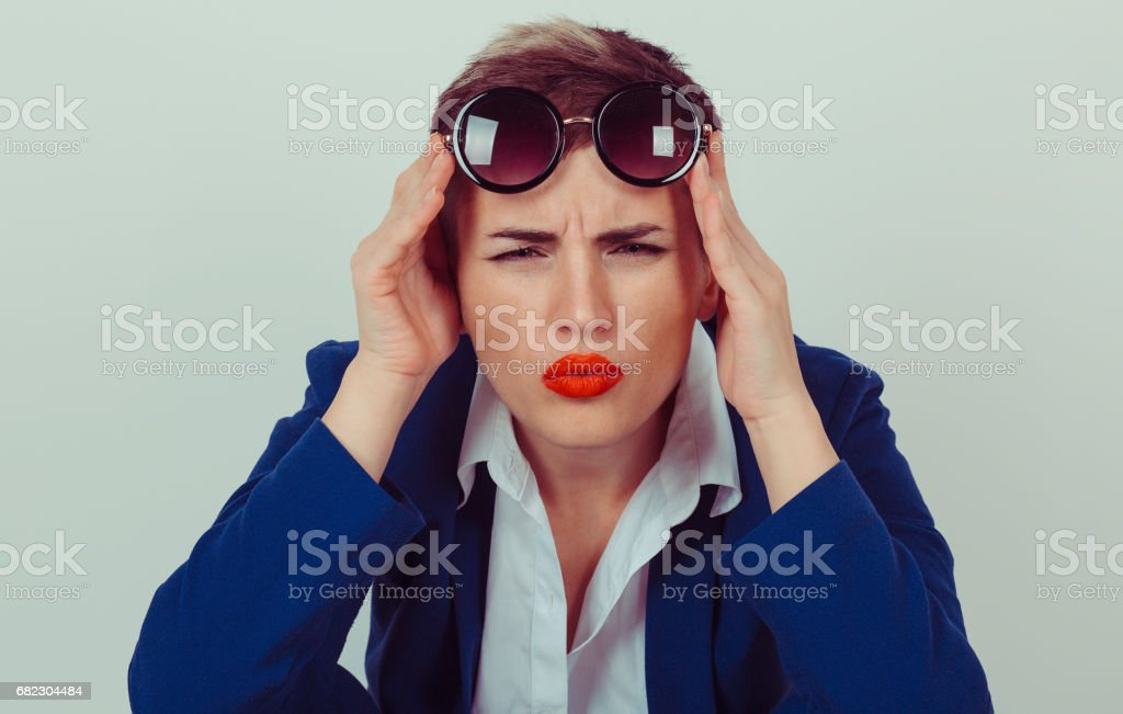 Head shot serious angry bitchy woman wife holding sunglasses up skeptically looking at you isolated green wall background blue suit white shirt. Human face expression body language attitude perception stock photo