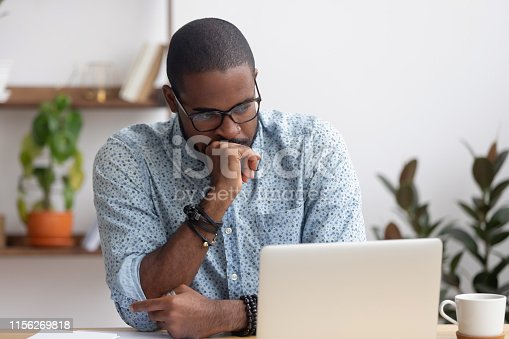 Head shot serious puzzled African American businessman looking at laptop screen sitting in office. Executive managing thinking received bad news keeping fist at chin waiting hoping positive result