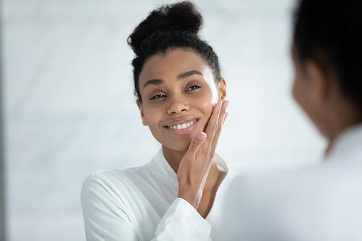 Head shot smiling African American woman touching cheek, enjoying perfect smooth face skin, looking in mirror, beautiful girl wearing white bathrobe doing facial massage in bathroom, skincare concept