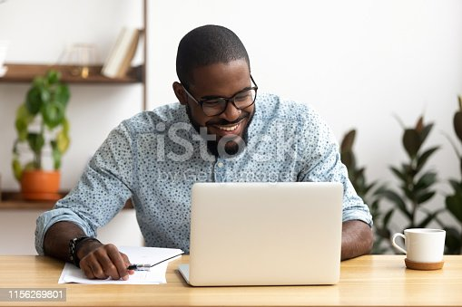 istock Head shot smiling african-american manager using laptop looking at screen 1156269801