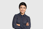 Head shot studio portrait millennial pleasant attractive smiling indian ethnicity confident student, young specialist, intern or employee looking at camera, isolated on grey studio background.