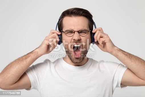 Head shot close up studio portrait young man enjoying favorite hard rock music track high quality sound, wearing wireless headphones, singing, having fun, isolated on grey white background.