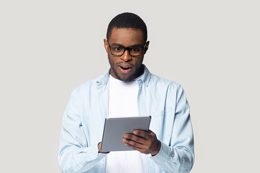Head shot close up surprised African American man looking at computer tablet screen, young male using electronic device, reading unexpected news in email, shopping offer, isolated on grey background
