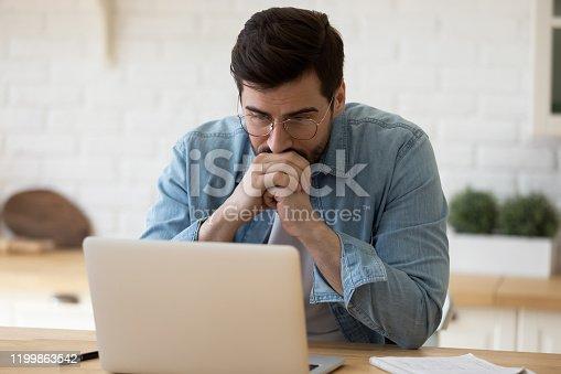 istock Head shot thoughtful businessman in eyewear looking at computer screen. 1199863542
