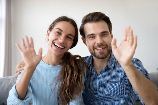 head shot woman and man waving hands looking at camera - sventolare la mano foto e immagini stock
