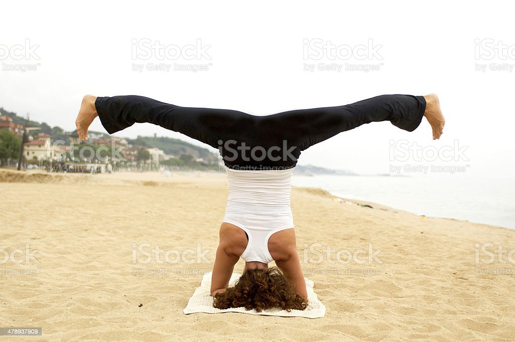Head stand yoga pose in the beach stock photo