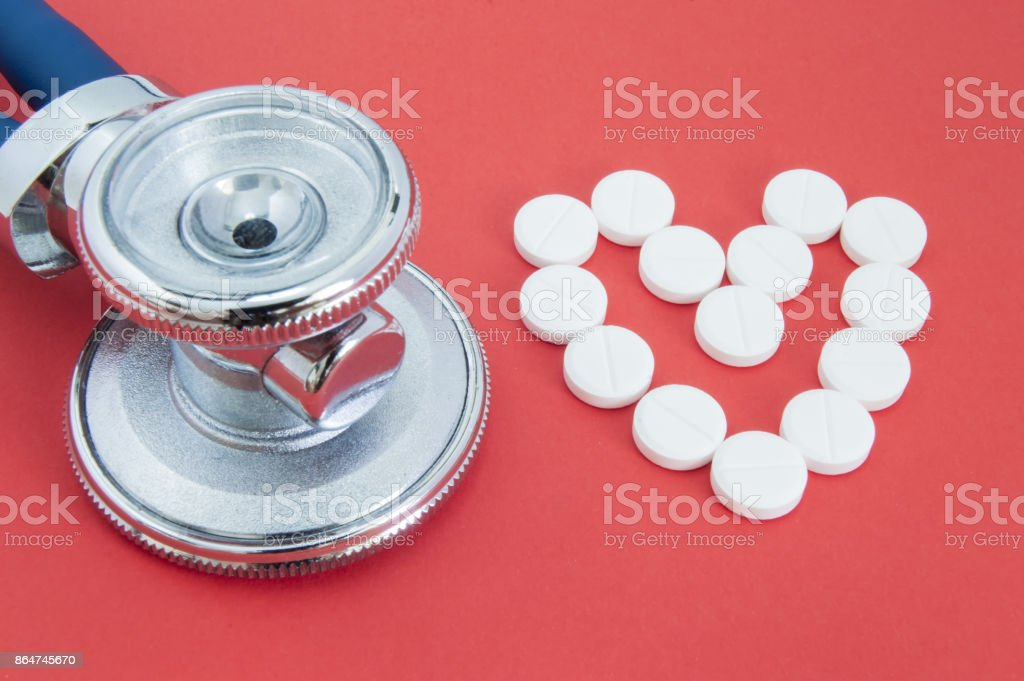 Head stethoscope and shape of the human heart, lined with white pills on red background. Stethoscope and heart of pills - idea for treatment and diagnosis in cardiology or cardiovascular direction stock photo