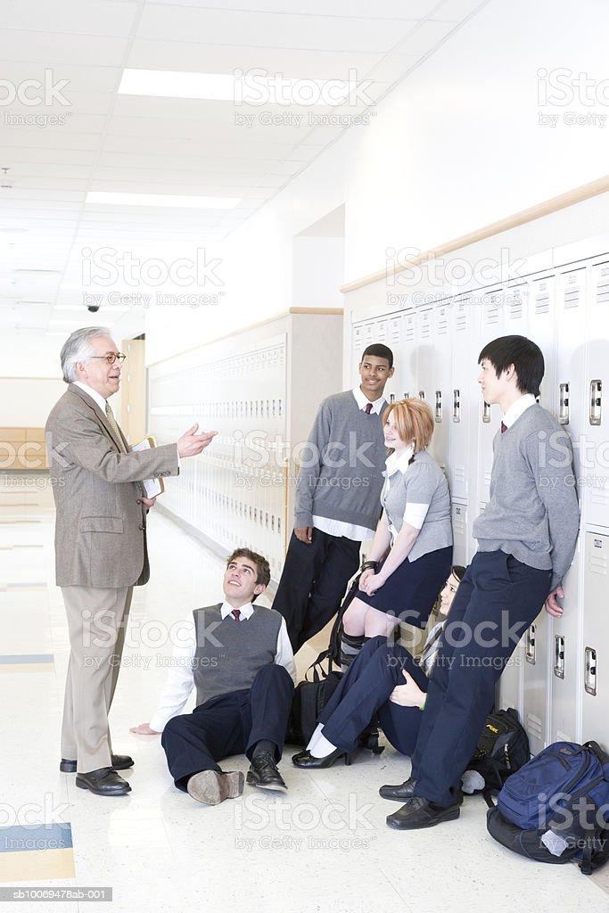 Maestro de hablar con los niños en edad escolar (15-19) in school corr foto de stock libre de derechos
