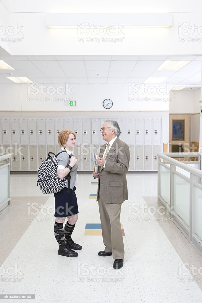 Head teacher talking with school girl (16-17) in school hallway royalty-free stock photo