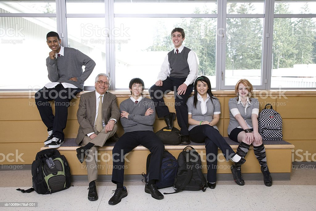 Head teacher with school children (15-19) sitting in school corridor, portrait royalty-free stock photo