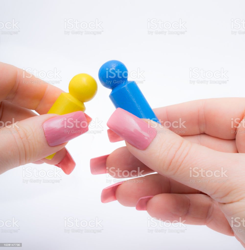 Two different pawns in a pink manicured hand ready to play a game