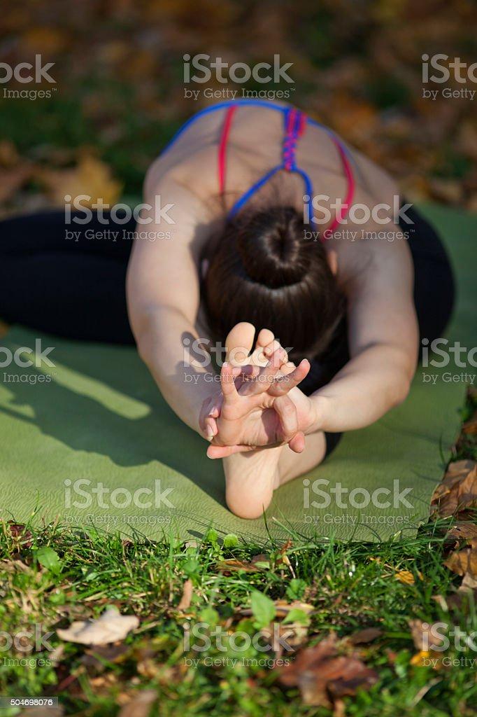 Head to knee forward bend yoga pose stock photo
