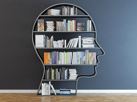 Head with a bookshelf in front of black wall