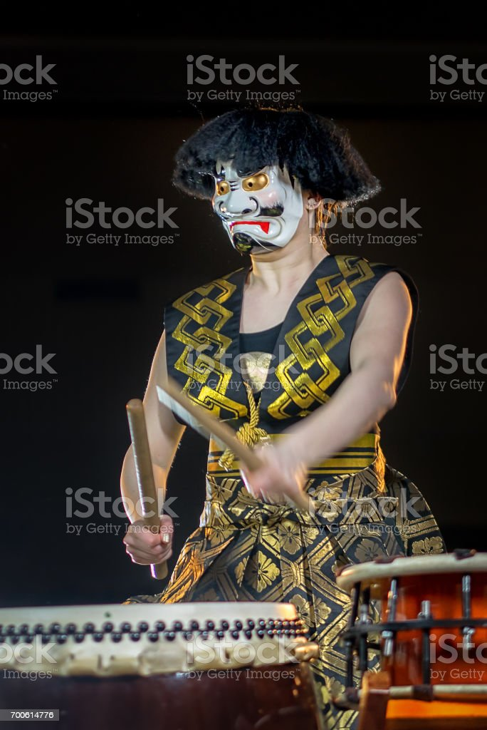 headache concept. devil drummer plays drumroll on the nerves. drummer girl in white demon mask with drumsticks, studio shot on a dark background. stock photo