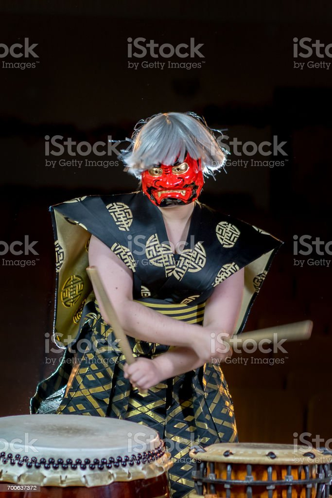 headache concept. devil drummer plays drumroll on the nerves. drummer girl in red demon mask with drumsticks, studio shot on a dark background. stock photo