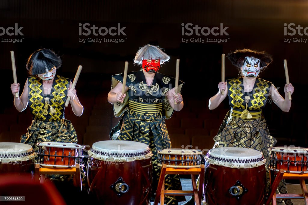 headache concept. three girl drummers in a white and red devil mesks play drumroll on the nerves. studio concert shot on a dark background. stock photo