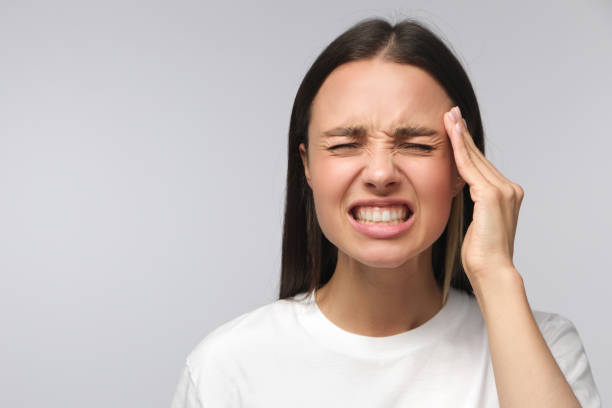 Headache concept. Young woman showing how much her head hurts, experiencing pain, looking miserable and exhausted, isolated on gray background Headache concept. Young woman showing how much her head hurts, experiencing pain, looking miserable and exhausted, isolated on gray background clenching teeth stock pictures, royalty-free photos & images