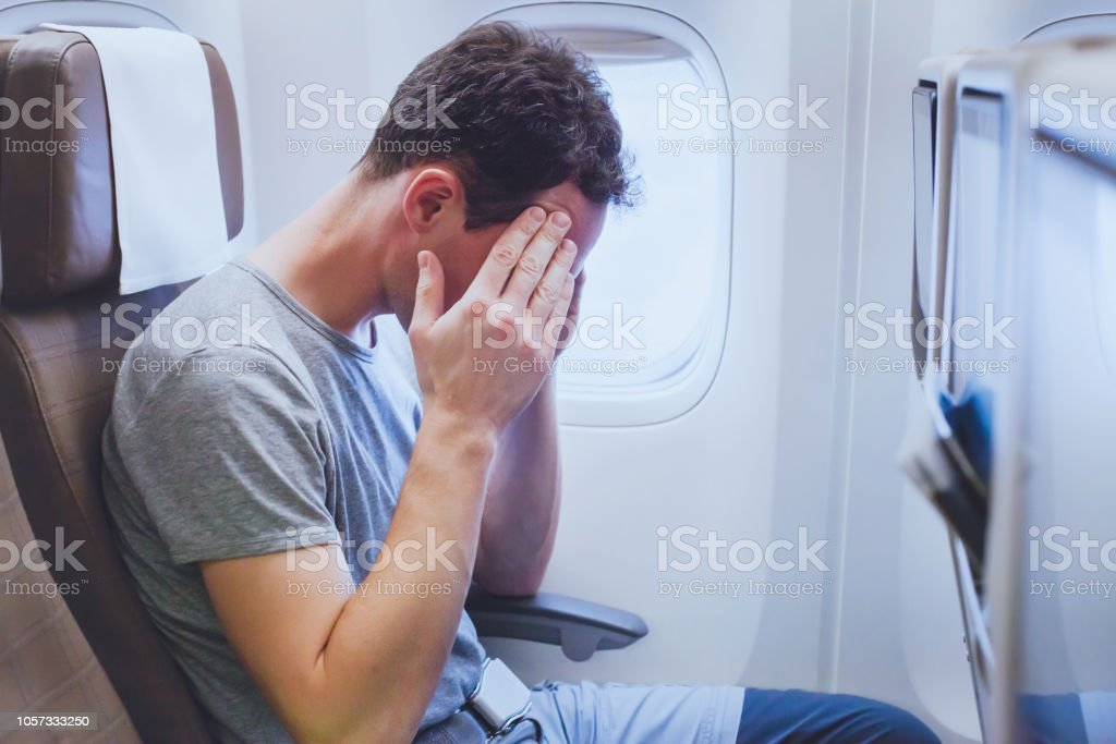 headache in the airplane, man passenger afraid and feeling bad during flight, fear stock photo