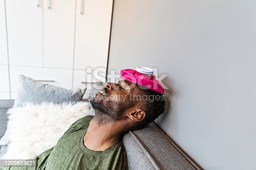 A young black man lying with ice pack on his head