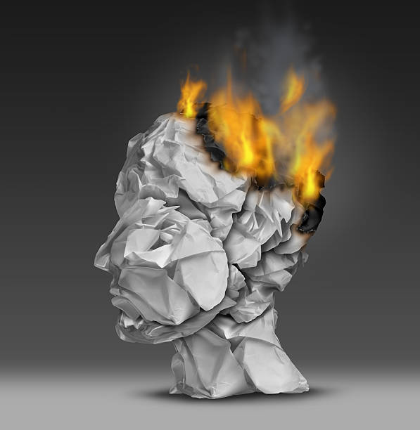 Headache Headache  and mental illness concept as a group of crumpled office paper shaped as a human head that is on fire burning away at the brain as a symbol and medical metaphor for emotional stress at work or degenerative dementia disease as alzheimers. mental burnout stock pictures, royalty-free photos & images