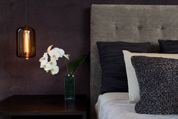 Headboard Detail with Pillows Lamp and Orchid Flowers Gray headboard detail of a bed with textured pillows, lamp and white orchid flower. luxury hotel room stock pictures, royalty-free photos & images