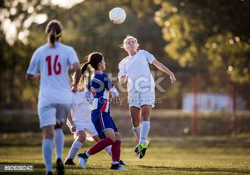 Teenage soccer player feeling determined after heading the ball before her opponent on a playing field.
