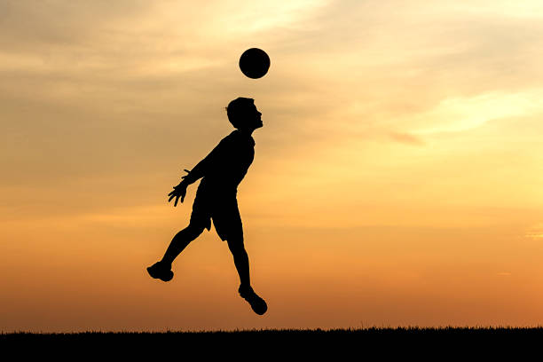 Heading the soccer ball at sunset. stock photo
