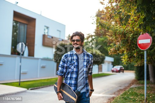 Attractive man with sunglasses carrying his skateboard while walking in the city.