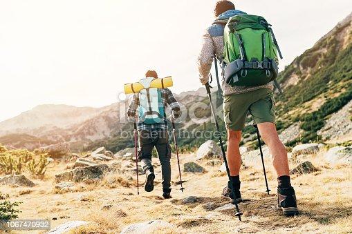 Two backpackers climbing a mountain